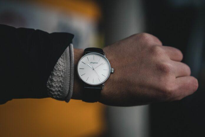 Mand har ur på hans håndled